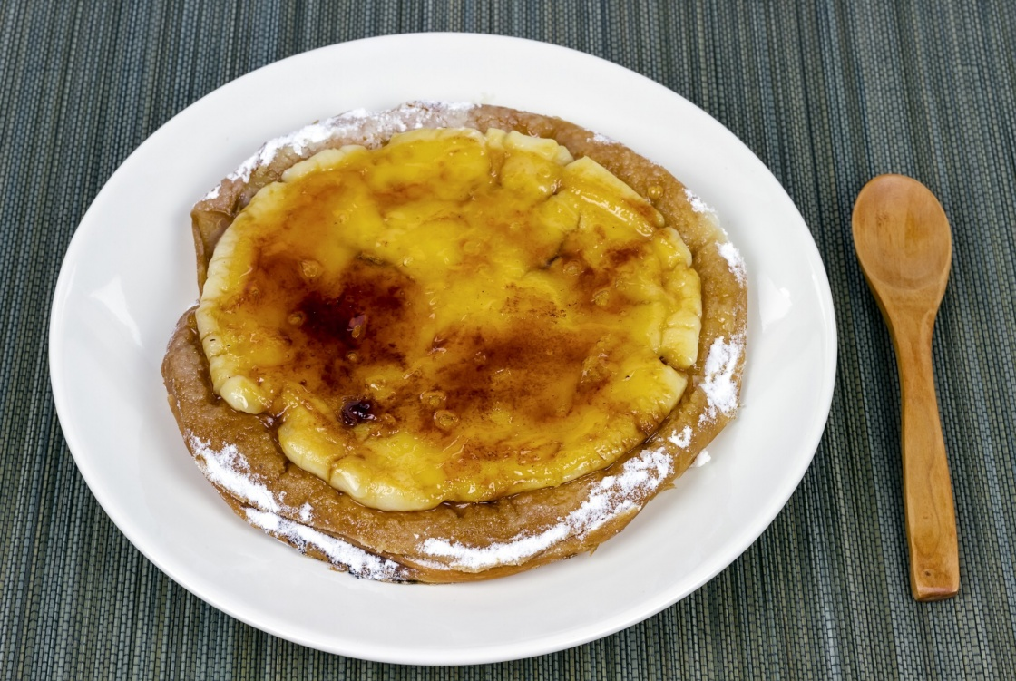 Typical ensaimada de Mallorca with a layer of burnt sugar and Catalan custard